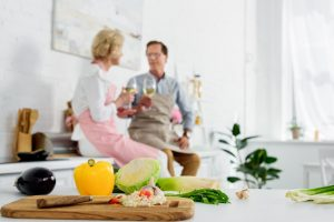 close-up view of fresh vegetables in wooden cutting board and senior couple drinking wine behind in kitchen